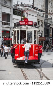 Istanbul, Turkey - July 1, 2016: Vintage red tram goes on Taksim square in Istanbul, boys ride for free on rear bumper