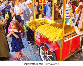 Istanbul, Turkey - July 11, 2018. A girl buying a corn cob at a street stall of Eminonu, a former district of Istanbul, Turkey.
