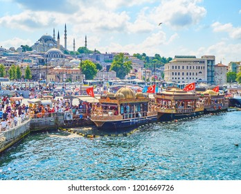 Istanbul, Turkey - July 11, 2018. The Fish Sandwich Boats moored in Eminonu Pier at the mouth of the Golden Horn Bay and the Eminonu district skyline with the Suleymaniye mosque in the background.