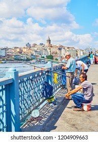 Istanbul, Turkey - July 11, 2018. Citizens on the Galata bridge fishing in the mouth of the Golden Horn Bay with a view of the Karakoy district skyline in the background. Istanbul, Turkey.