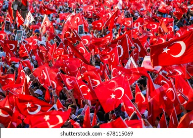 ISTANBUL, TURKEY - JULY 15: People, waving Turkish flags, attend a ceremony to commemorate the one year anniversary of the July 15, 2016 failed coup attempt on July 15, 2017 in Istanbul, Turkey.