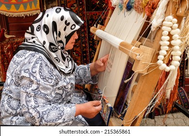 ISTANBUL, TURKEY - JULY 18, 2014: A woman hand weaves an oriental silk rug.  Hand woven carpets are beautiful works of art which require great skill to produce.
