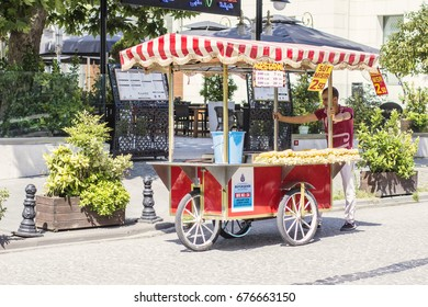 ISTANBUL, TURKEY - July 2017: Turkish man on street at Sultan Ahmet area selling grilled corn from traditional red cart, Istanbul, Turkey
