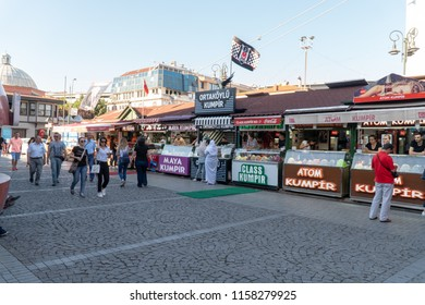 Istanbul, Turkey - July 2018 : Many kiosks offer traditional Turkish fastfood, lively area at day time in famous Ortakoy pier area. Vendors tout passers to try or eat sweet waffle and backed potato