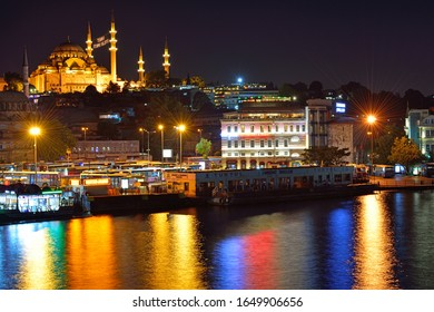 Istanbul, Turkey - July 23, 2015: Istanbul at night with Suleymaniye Mosque and beautiful multi-colored reflections in the water of the Golden Horn Bay. View from Galata Bridge.