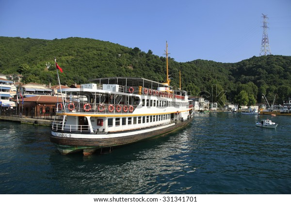 ISTANBUL, TURKEY, JULY 26, 2015 :Passenger ferry and houses at the coastline of Anadolu Kavagi, a famous fishing town at the edge of Bosphorus with many restaurants and touristic facilities.
