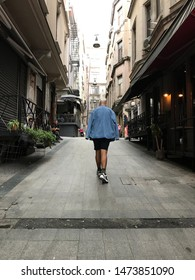 Istanbul, Turkey - July 28, 2019: Unidentified young man walking up the streets of Asmalimescit district in Beyoglu., Istanbul. Asmalimescit is a popular touristic spot with cafes and bars.