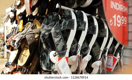 Istanbul, Turkey - July 4, 2018: A collection of slippers in FLO store in Mall of Istanbul, and the advertising sign of discounts and price in Turkish in Mall of Istanbul