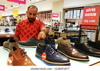 Istanbul, Turkey - July 4, 2018: a man stands to choose and buy a shoe from a collection put on a shelf in FLO store in Mall of Istanbul
