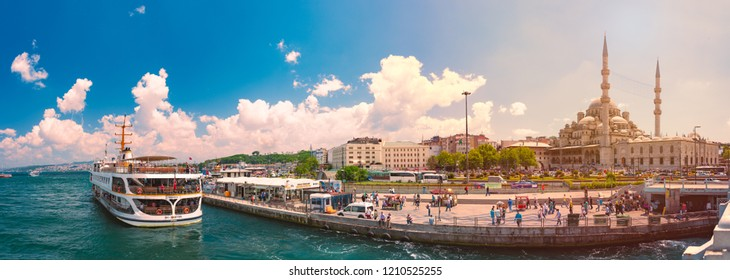 ISTANBUL, TURKEY - JULY 5, 2014: Yeni Cami Ottoman imperial mosque located in the Eminönü quarter of Istanbul, Turkey. Strait of Bosporus with ships in foreground and blue cloudy sky in background.