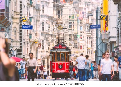 ISTANBUL, TURKEY - JULY 5, 2014: Old red tram in Taksim, Beyoğlu, Istanbul, Turkey. Historical Istiklal street in city centre with people walking around.