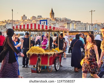 Istanbul, Turkey - July 7, 2018. Corn cobs stall in a street of Eminonu, a former district of Istanbul, Turkey, with the Galata Tower in the background at sunset.
