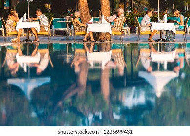 ISTANBUL, TURKEY - JULY 9, 2014: people dining at hotel near pool. Chairs and table near pool at hotel restaurant. Cutlery and napkings on tables. Resort life on holidays.