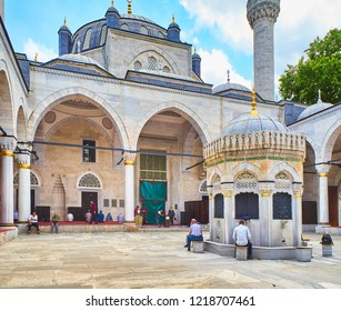 Istanbul, Turkey - July 9, 2018. Muslims in the courtyard of The Yeni Valide Camii Mosque, with the Ablution fountain in the foreground. Uskudar district, Istanbul, Turkey.