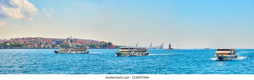 Istanbul, Turkey - July 9, 2018. Ferryboats crossing the Bosphorus, with the Eminonu neighborhood skyline and The Maiden's Tower in the background. Istanbul, Turkey.