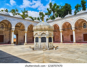 Istanbul, Turkey - July 9, 2018. The courtyard of The Yeni Valide Camii Mosque, with the Ablution fountain in the foreground. Uskudar district, Istanbul, Turkey.