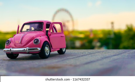 Istanbul / Turkey - Jun 11 2018: Macro shot of a pink car and beautiful landscape background. Retro car model on white ground. Toy model car Volkswagen Beetle. Vintage car model. Old retro beetle.