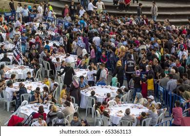 ISTANBUL, TURKEY - JUNE 03, 2017: Rows of tables set up for Ramadan and people waiting the Iftar food near the Zeytinburnu, Istanbul, Turkey.