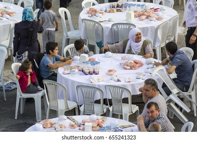 ISTANBUL, TURKEY - JUNE 03, 2017: Rows of tables set up for Ramadan and people waiting the evening meal (Iftar) food near the Zeytinburnu, Istanbul, Turkey.