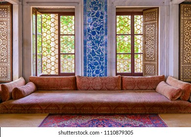ISTANBUL, TURKEY - JUNE 10, 2018 : View of classical oriental design home with low sofa, calligraphy pattern art on walls and a window at Topkapi Palace of istanbul.