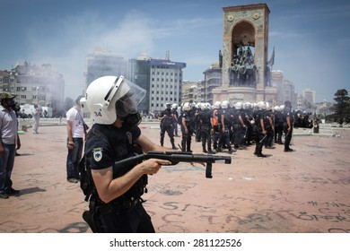 Istanbul, Turkey - June 11, 2013: A riot police officer shoots a gas canister at protesters in Taksim Square.