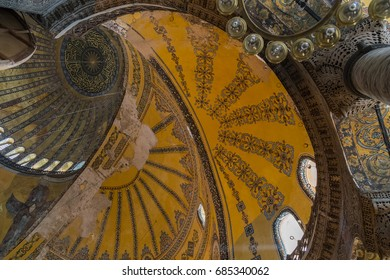 ISTANBUL, TURKEY - JUNE 11, 2014: Interior view of Hagia Sofia (Aya Sofya) Mosque in Istanbul, Turkey. Abstract shot on ceiling with ornamental huge domes and arches.