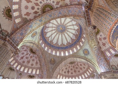 ISTANBUL, TURKEY - JUNE 11, 2014: Interior of the Blue Mosque (Sultan Ahmed mosque), an Ottoman imperial mosque in Istanbul, Turkey. Abstract shot of the hand-painted main dome, semi-domes and arches.
