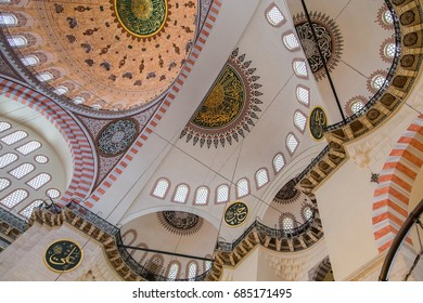 ISTANBUL, TURKEY - JUNE 12, 2014: Interior of Suleymaniye Mosque, an Ottoman medieval imperial mosque at the Third hill of Istanbul. Abstract shot of the ceiling with colorful huge dome and arches.