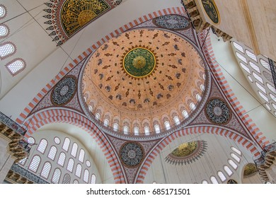 ISTANBUL, TURKEY - JUNE 12, 2014:  Interior of Suleymaniye Mosque, an Ottoman imperial mosque at the Third hill of Istanbul. Abstract shot of the colorful dome and arches with stained glass windows.