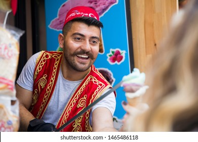 ISTANBUL, TURKEY - JUNE 15, 2019: Unidentified seller of Turkish ice cream at Istanbul, Turkey. Traditional Turkish ice cream was made with salep, produced by orchid flowers.