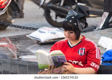Istanbul, Turkey - June 19, 2013: Young woman sitting and reading book during the Gezi Park protests.