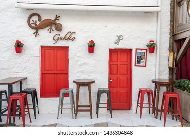 ISTANBUL, TURKEY - JUNE 20, 2019: Small white cafe with red doors and red shutters in the colorful and trendy happening area of Balat with some chairs outside on the terrace