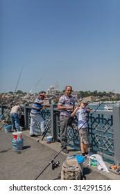 ISTANBUL, TURKEY - JUNE 20: Unidentified Turkish fishermen fishing on Galata Bridge on June 20, 2015 in Istanbul, Turkey