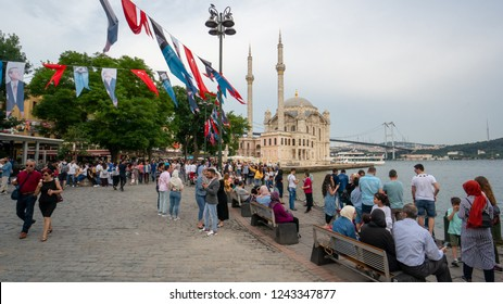 istanbul, Turkey - June 2018: People spend time and enjoy the view in Ortakoy with the mosque and bosphorus