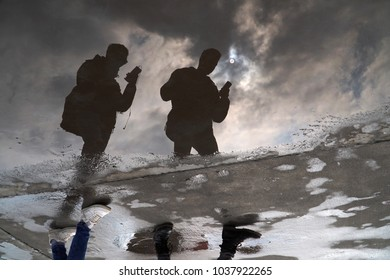 Istanbul, Turkey - March 1, 2018 : Reflections of two men in water, they are looking at mobile phones when they are walking. Beautiful clouds and sun are reflecting in the water too.