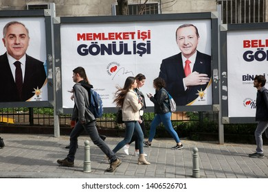 ISTANBUL, TURKEY - March 10, 2018: People walk past by AK Party billboards with pictures of Turkish President Tayyip Erdogan and mayoral candidate Binali Yildirim in Istanbul, Turkey.