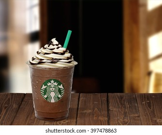 ISTANBUL, TURKEY - March 15, 2016: Cup of Starbucks Frappuccino on wooden table in Starbucks cafe. Starbucks is the World's largest coffee house.