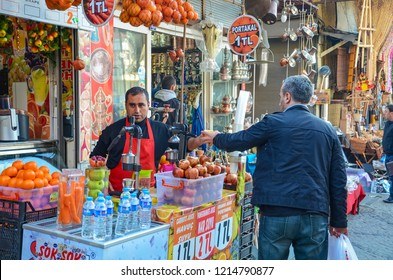 ISTANBUL, TURKEY - MARCH, 2012: Street food seller serving oranges and other fruits in Istanbul, Turkey