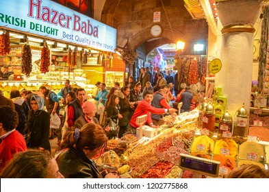 ISTANBUL, TURKEY - MARCH, 2012: Traditional Turkish delight sweets, dried fruits, nuts at the Spice Market. People shopping in the Grand Bazar, one of the largest covered markets in the world