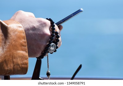 Istanbul, Turkey. March 23 2019. A close up of a muslim man's hands holding islamic prayer beads, together with his smart phone and sun glasses, as he travels by ferry to the mosque for Friday Prayers