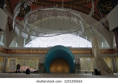 Istanbul, Turkey - March 3, 2013. Interior view of Sakirin mosque in Istanbul, turquoise and gold mihrab and dripping glass chandelier, people and Arabic inscriptions.