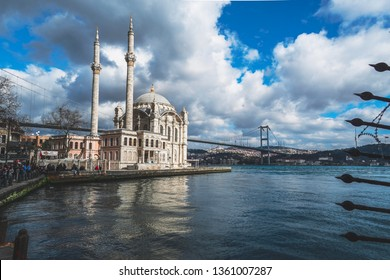 Istanbul / Turkey - March 30 2019 : Classical photo of Ortakoy region of Istanbul. Ortakoy Mosque, Bosphorus Bridge and new Camlica Mosque at the back.