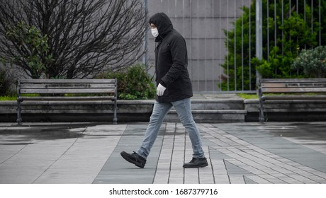 ISTANBUL / TURKEY - MARCH 30, 2020:  A man wearing medical face mask and gloves while walking on the square. The new type of Coronavirus (COVID-19) pandemic has been affected the Turkey.