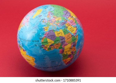 ISTANBUL, TURKEY - MARCH 30, 2020. Reduced model of the Earth World globe atlas on the red background.