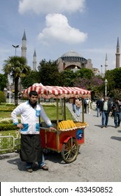 ISTANBUL, TURKEY - MAY 04, 2009: A street vendor of roasted corn in gardens Sultanahmet and view of Haghia Sophia in Istanbul