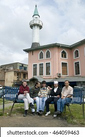 ISTANBUL, TURKEY - MAY 04, 2009: Workers at a time of rest, smoking and talking on a bench near a mosque in Eminonu