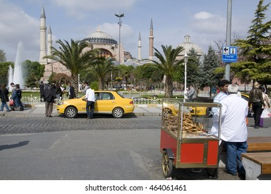 ISTANBUL, TURKEY - MAY 04, 2009: Street vendor bread , taxi and people strolling through the gardens, near the church Hagia Sophia