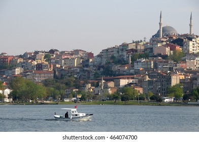 ISTANBUL, TURKEY - MAY 04, 2009: Small boat sails along the Bosphorus river at sunset, with the city and mosques background