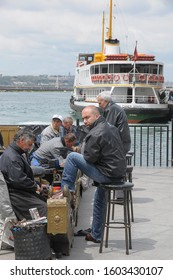 Istanbul, Turkey - May 05, 2009: Men cleaning their shoes with shoeshine shoes with a boat docked in the port of Haydarpasa, in the blurred background on the Asian side of the city