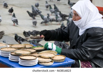 ISTANBUL, TURKEY - MAY 05, 2009: Woman selling food for pigeons , at the door of the mosque Yeni Camii